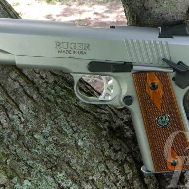The Ruger SR1911 CMD .45 with a Two-Tone soft gray green treatment with brown grip against a log