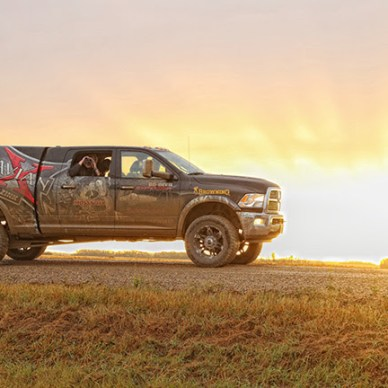 Camouflaged pickup truck with morning sun behind it