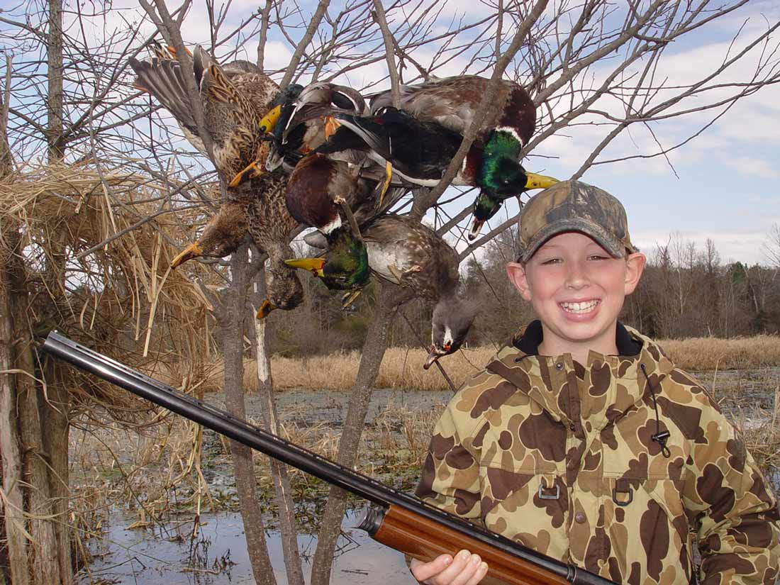 young boy smiling, holding his shotgun with downed ducks in the background.