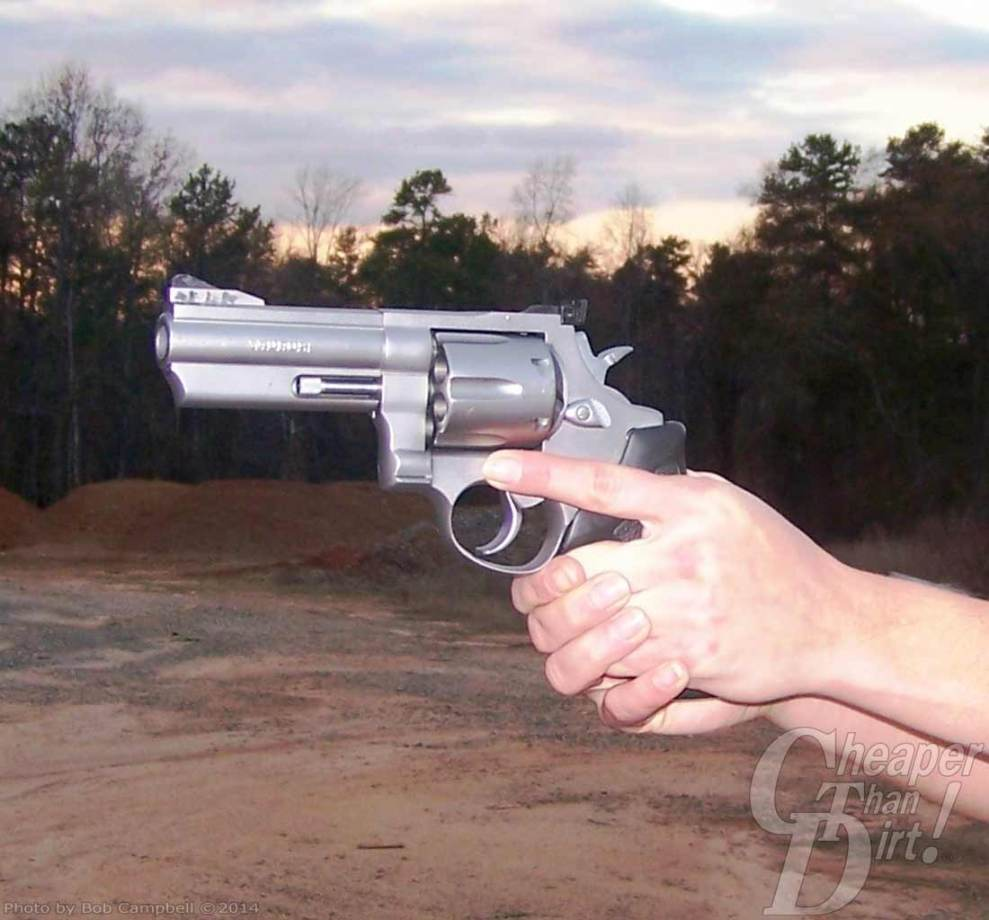 A Taurus .44 Magnum being held in both hands of a person, barrel pointed left with dirt in the foreground and trees in the background.