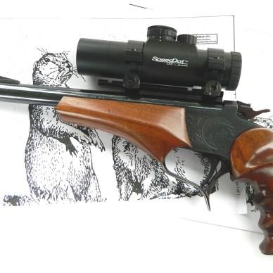 Thompson Center Contender handgun left on groundhog paper target