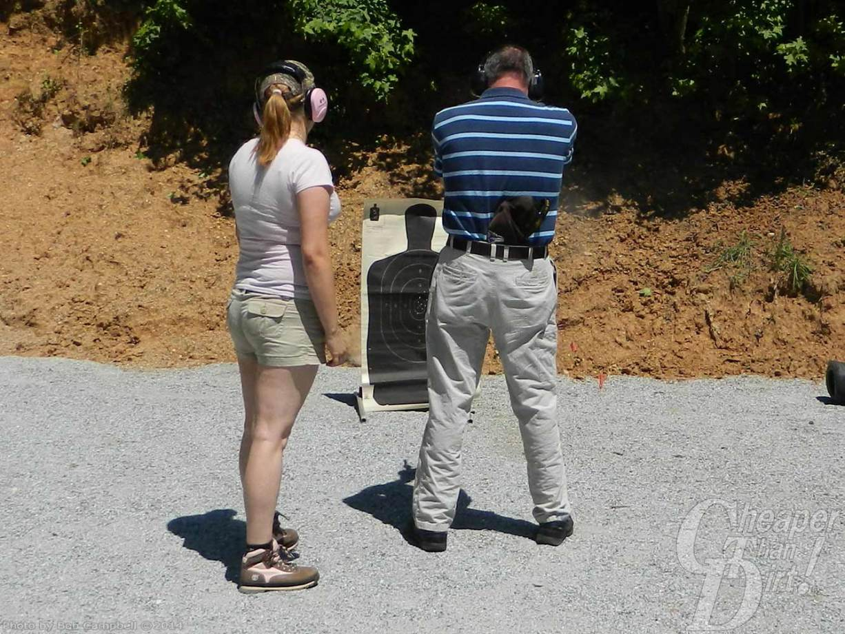 Young woman in light shirt and shorts with a young man in a striped blue shirt and light pants practice shooting a target at close range.