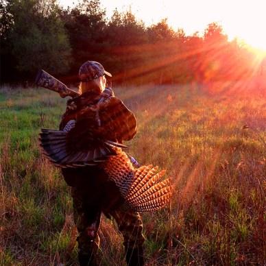 female hunter with shotgun over shoulder and wild turkey