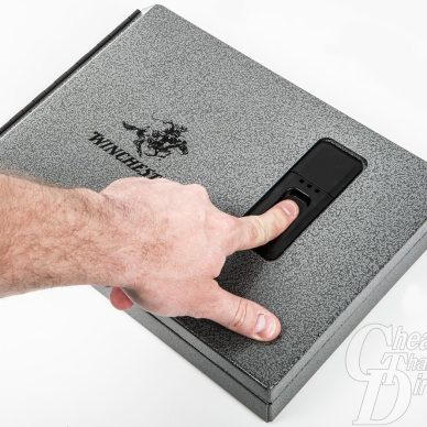 Picture shows a man swiping his finger on a biometric safe.