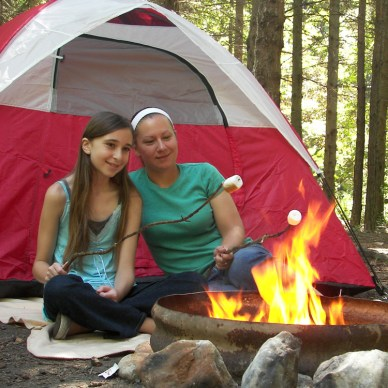 Two girls are roasting marshmallows in front of a tent.