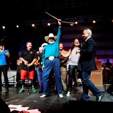 Charlie Daniels holding up a special edition Henry lever-action rifle