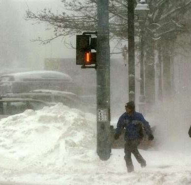 Two men crossing the street during a blizzard.