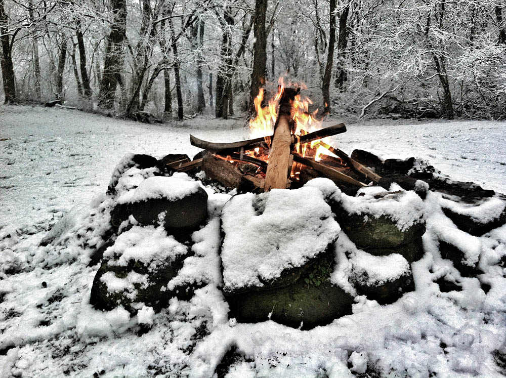 Picture shows a fire ring made of large rocks, a tee pee-style fire in the woods covered in snow.