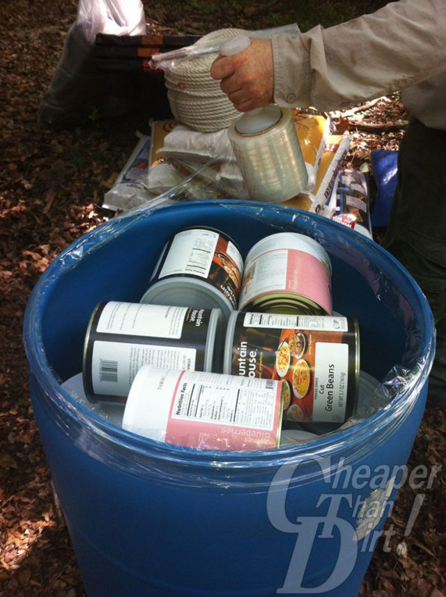 Picture shows a 55-gallopn drum filled with #10 cans of food