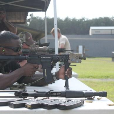 A man is summer shooting a rifle at an outdoor gun range.