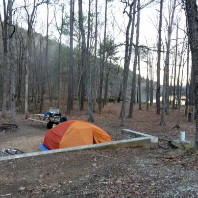 Picture shows a bright orange tent in a state park in winter.