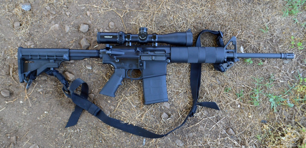 Del Ton DT 10 AR-10 rifle with scope and sling on a dirt background