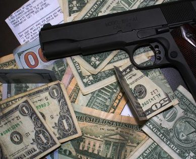 Handgun on top of a pile of U.S. Currency