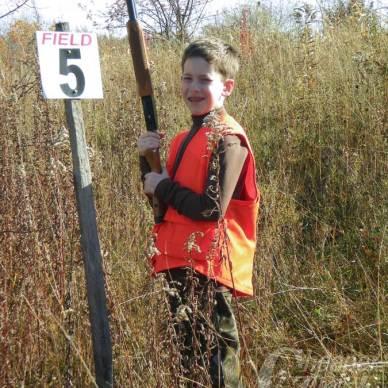 youth wearing orange safety vest and shotgun