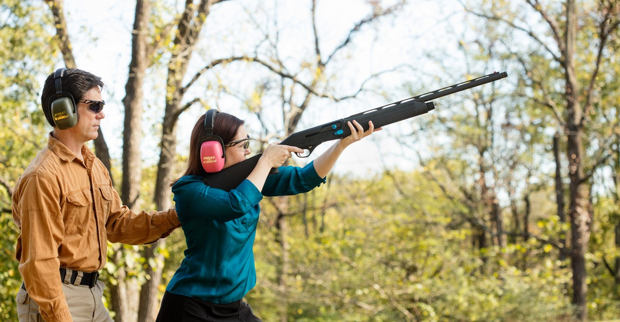 Woman wearing pink ear muffs shooting the Stoeger M3K 12 gauge shotgun