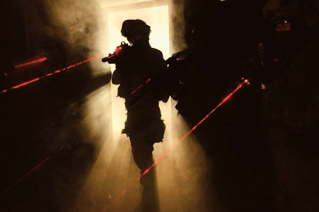 SWAT team members raiding a house with red lasers