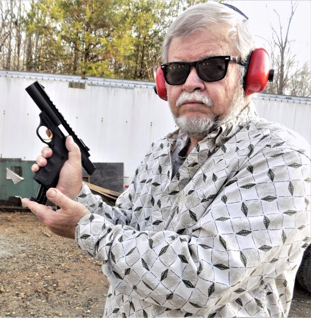 Bob Campbell holding a Browning Buckmark pistol while wearing red hearing protection