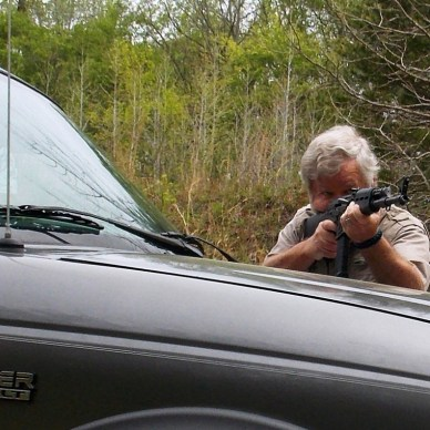 Bob Campbell shooting an AK-47-type rifle over the hood of a truck