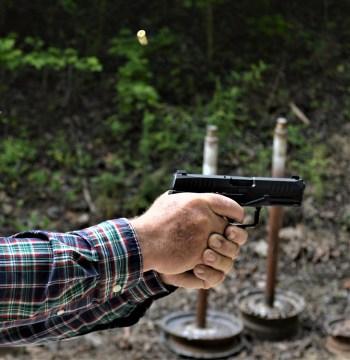 Man's hands holding the Arex Rex Delta pistol