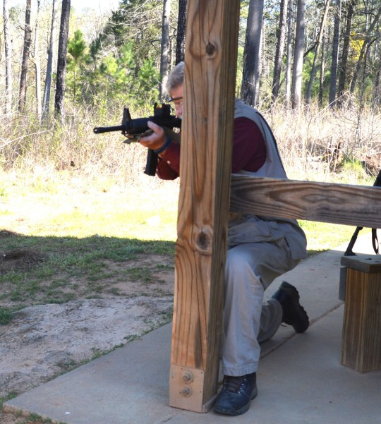 Bob Campbell shooting a rifle from a kneeling stance behind a wooden post