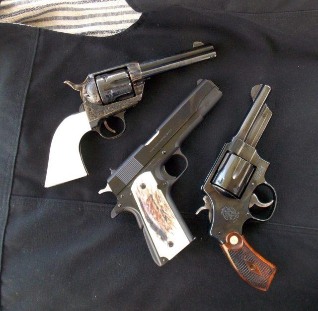 three handguns, two revolvers and a pistol guns for hiking