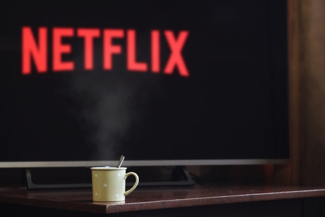 coffee on table with tv with netflix logo