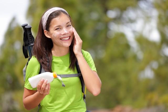 woman applying sunblock on hike