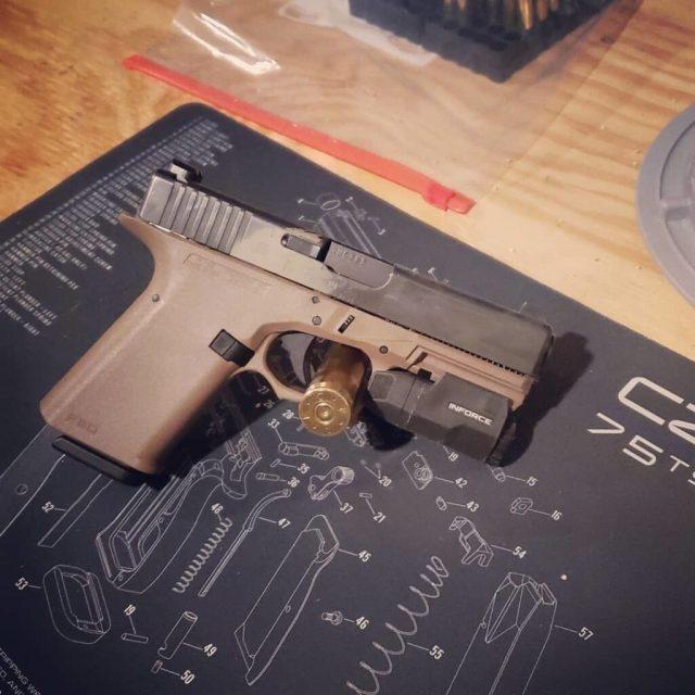 Brown GLOCK pistol on shop mat