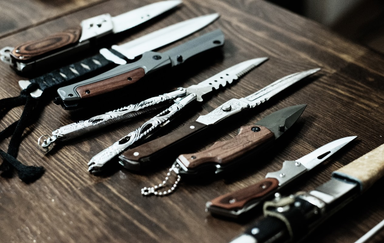 many different budget edc knives on wooden table