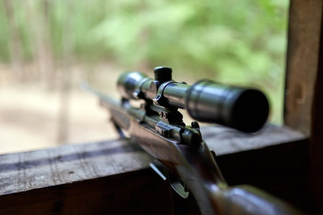 Hunting rifle with optical scope in blind