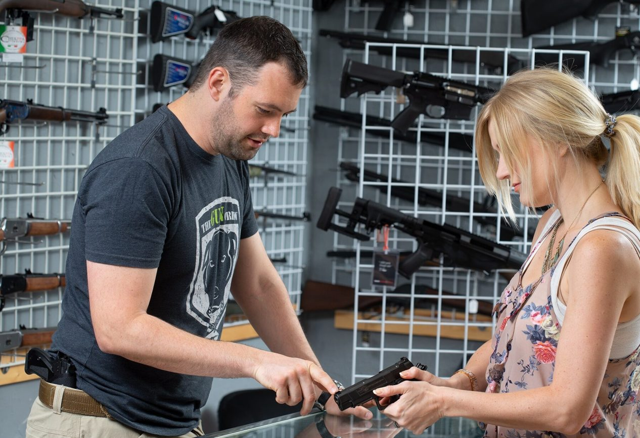 Man helping woman choose new gun