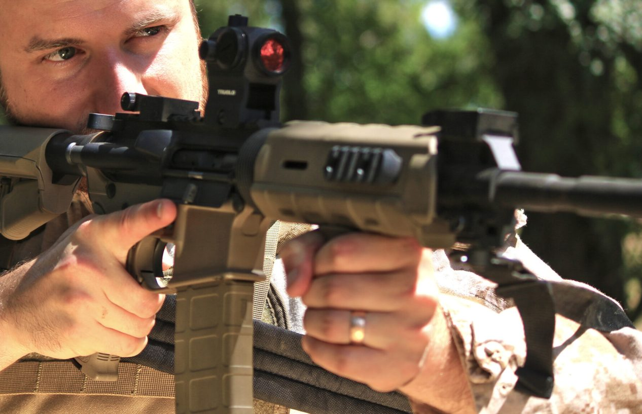 man shooting ar-15 with red dot sight