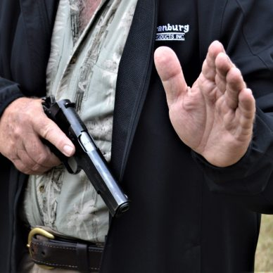 man drawing pistol with arm out