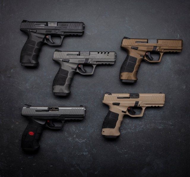 Five pistols on black table