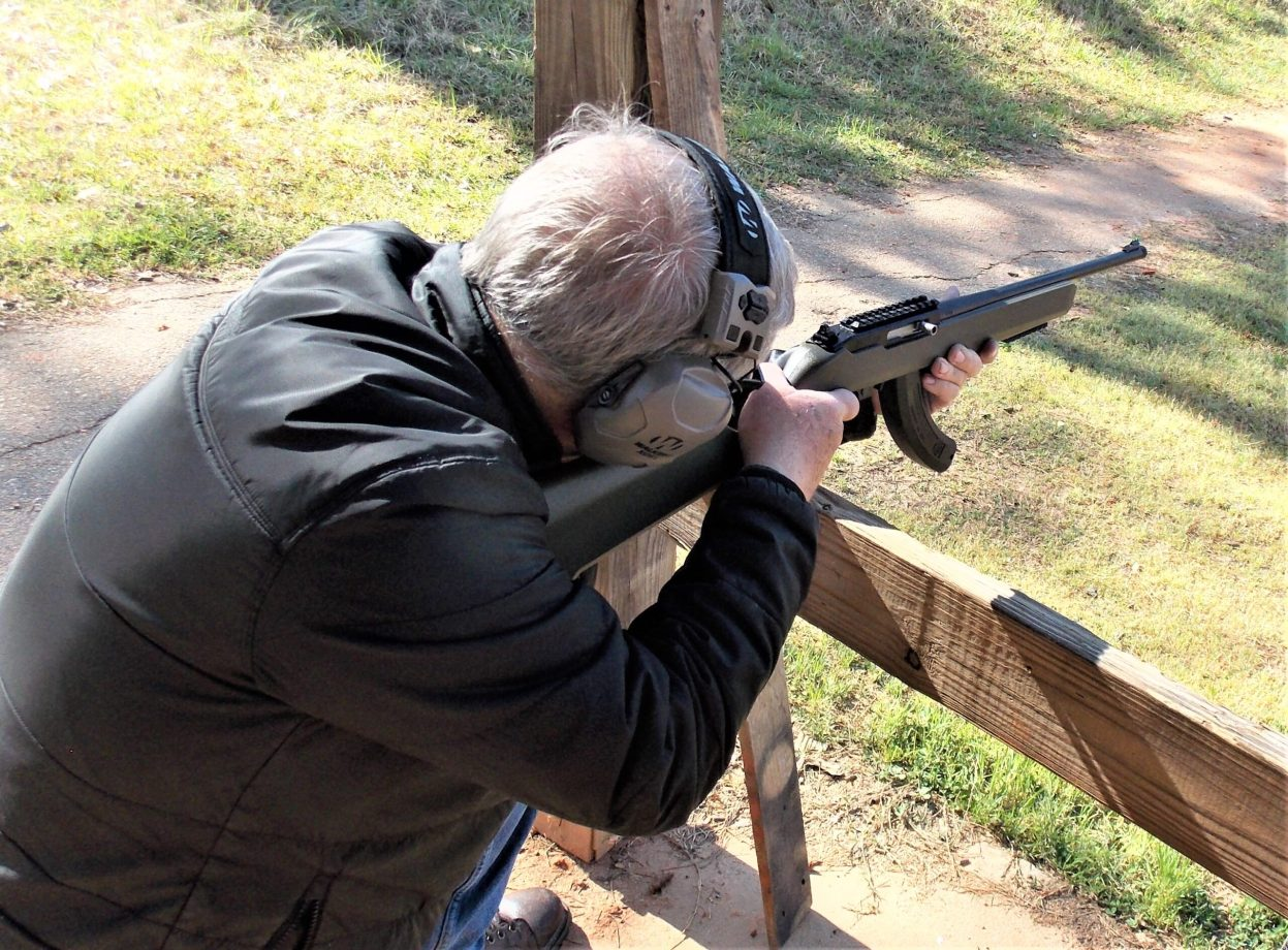 man resting rifle on fence firing rifle