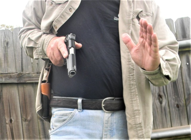 man drawing pistol