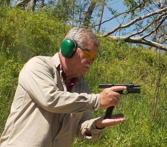man racking slide and reloading pistol