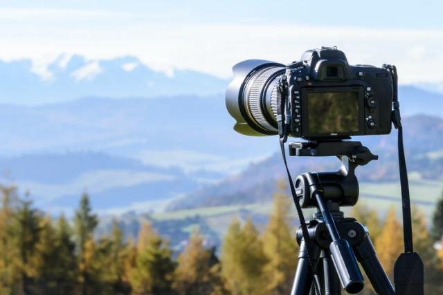 camera on tripod facing woods and mountains