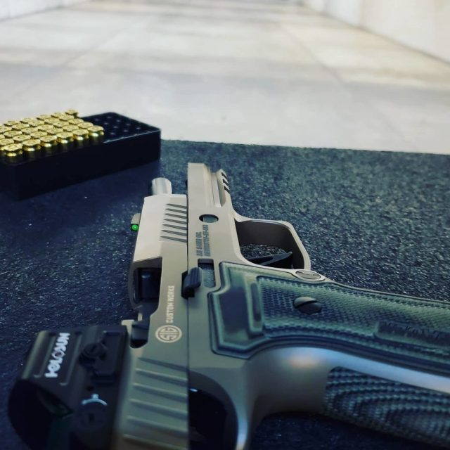 SIG AXG pistol with red dot on range bench