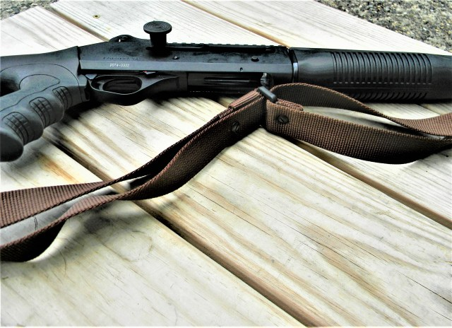 Shotgun with sling on wood table