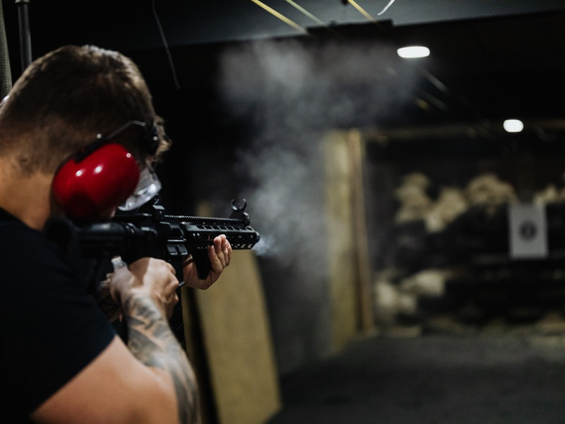 Man shooting rifle with ear protection