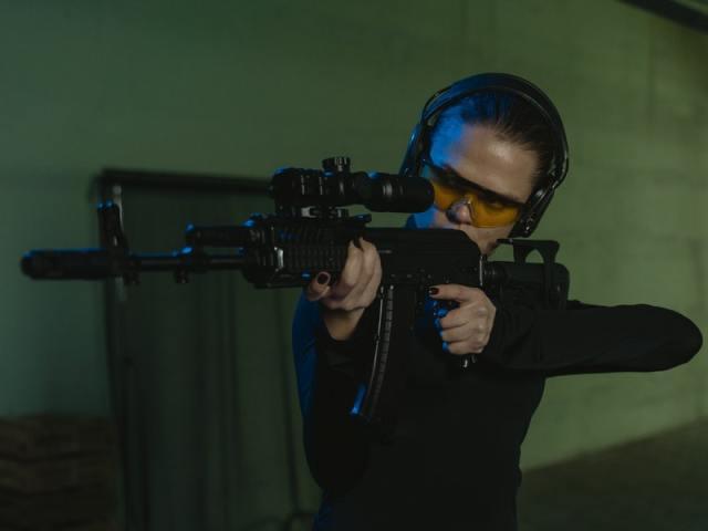 woman shooting rifle with ear protection