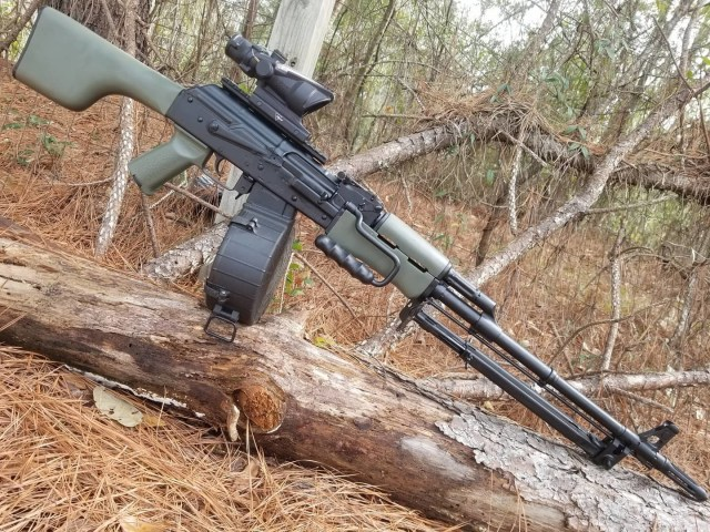 AK rifle on Log