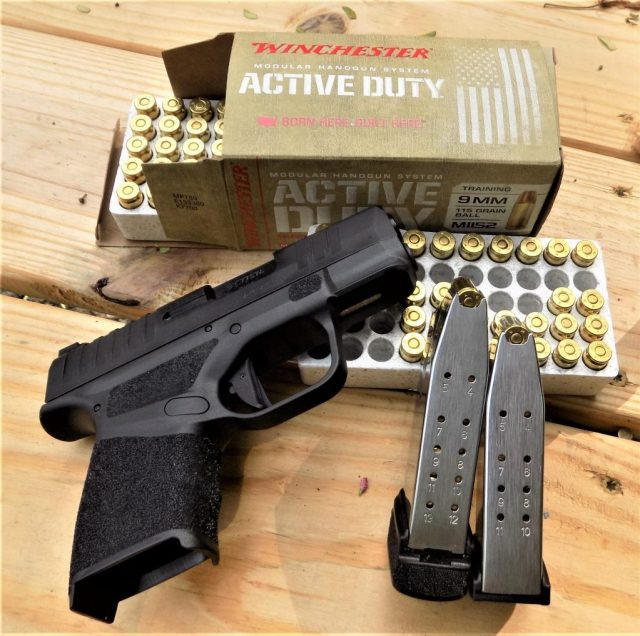 Springfield Armory Hellcat on wood table with ammo best 9mm pistols