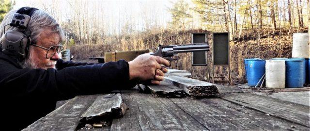 man shooting revolver at range bench