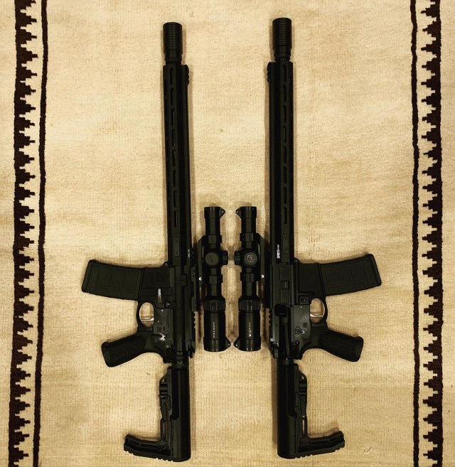 two AR-15s mirrored on rug