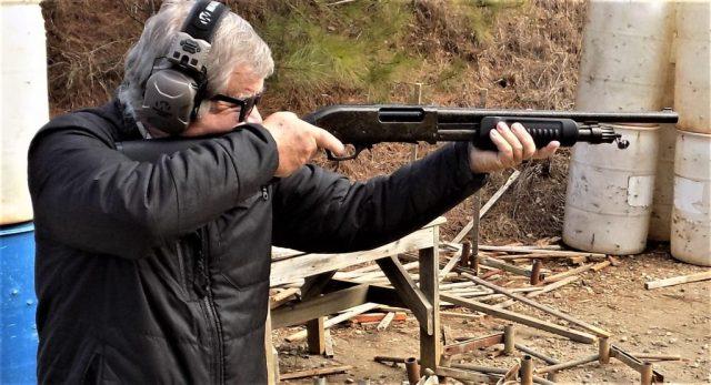 Man shooting Iver Johnson pump-action shotgun