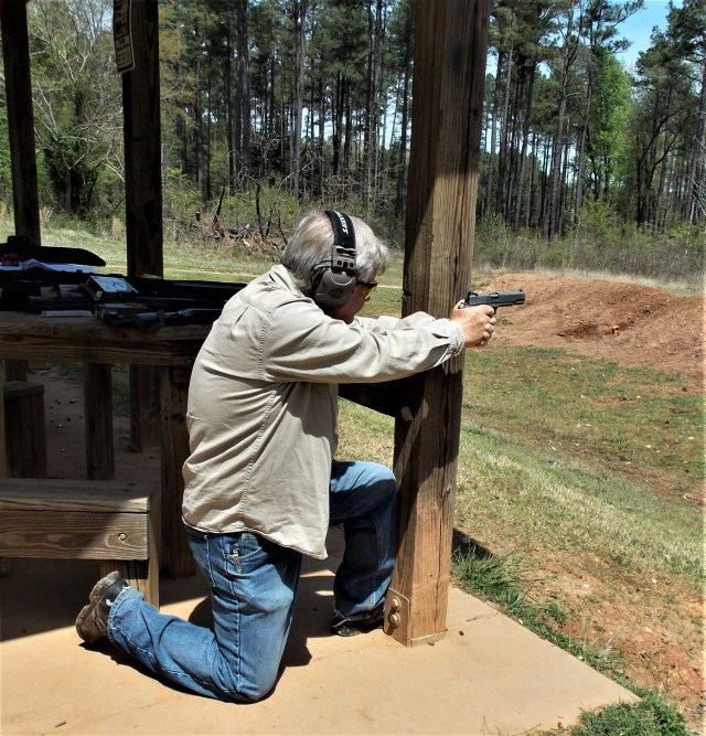 man training kneeling and shooting behind cover
