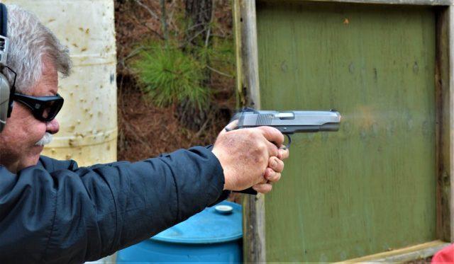 man firing pistol
