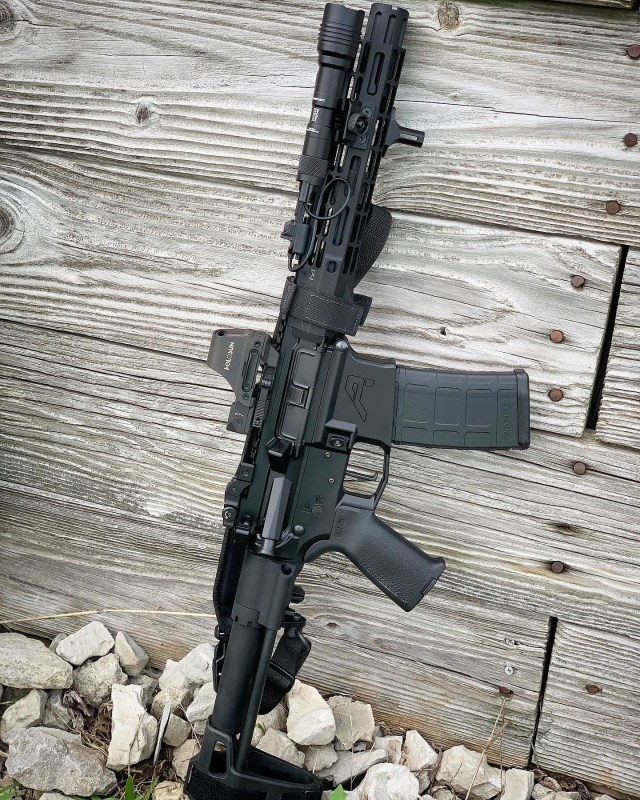 AR-15 pistol with light and red dot sight leaning on wood
